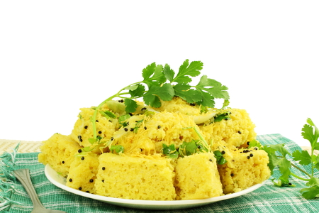 sev: khaman dhokla traditional gujrati indian snack food dish in white background