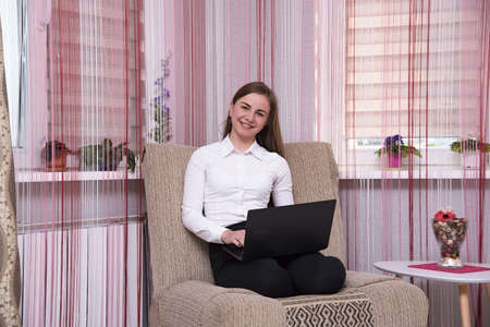 Im a freelancer and I love working at home. Portrait of a beautiful brunette freelancer girl working on a laptop at home on the sofa. She sits right in front of the camera smiling and looks happy