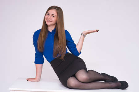 portrait of a beautiful brunette girl sitting on a table on a white background. She sits right in front of the camera, smiling and pointing at the product.