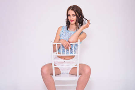 Im glad to see you. Portrait of a beautiful brunette girl on a white background in a T-shirt on a chair. She is standing right in front of the camera smiling and looking happy