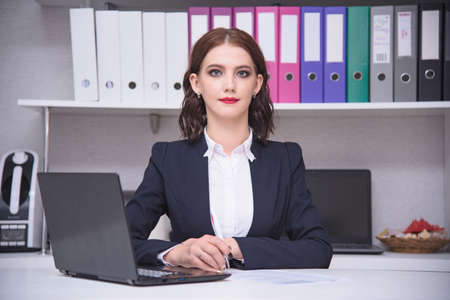 I work in the office. Portrait of a beautiful brunette manager girl in an office working behind a laptop. She sits right in front of the camera smiling and looks serious Stock Photo