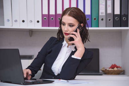 I work in the office. Portrait of a beautiful brunette manager girl in an office working behind a laptop with a smartphone. She sits right in front of the camera smiling and looks serious Stock Photo