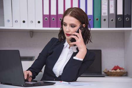 Je travaille au bureau. Portrait d'une belle fille brune manager dans un bureau travaillant derrière un ordinateur portable avec un smartphone. Elle est assise juste devant la caméra en souriant et a l'air sérieuse Banque d'images