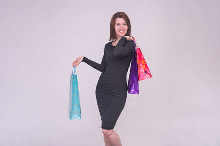 I love shopping. Portrait of a beautiful brunette girl in a dress on a white background with packages from a store. She is standing right in front of the camera smiling and looking happy