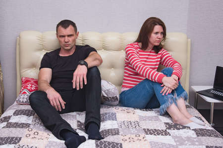 family conflict. Portrait of husband and wife during family difficulties and problems of disputes and conflicts. They are right in front of the camera and look unsatisfied