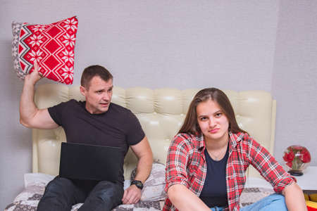 portrait of the father and daughter with family problems, family difficulties in family relationships in the room on the bed. They are right in front of the camera and look unhappy Stock Photo