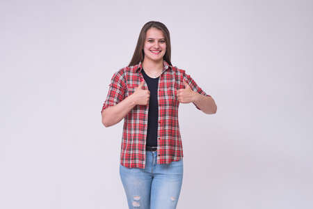 portrait of a beautiful brunette girl on a white background in jeans in different poses with different emotions. She is standing right in front of the camera smiling and looking happy