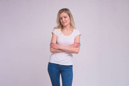 portrait of a beautiful blonde girl on a white background in different poses with different emotions. She is standing right in front of the camera smiling and looking happy