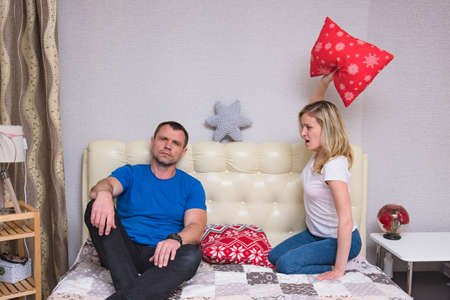 family relationships. Portrait of husband and wife: family quarrels, problems, family difficulties, family relationships in the room. They sit in front of the camera and look unhappy