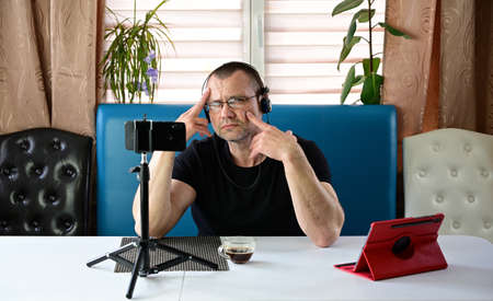 Portrait of an adult man in headphones and glasses talking while holding a video conference via smartphone and tablet at home.