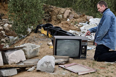 Photo of a caucasian man in the trash in a sad mood. Environmental protection concept