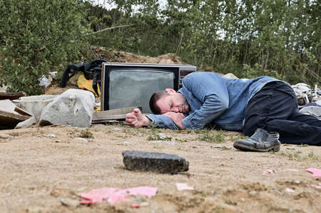 Photo of a homeless man on the background of trash and garbage outdoors. Model is lying on the ground and looking at the camera.