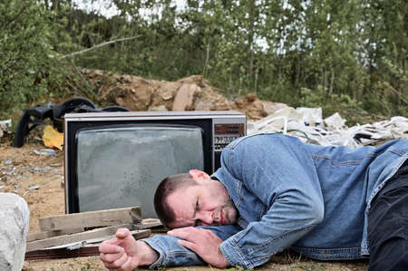 The model is lying on the ground and looking at the camera. Photo of a homeless man on the background of the TV and trash and garbage outdoors