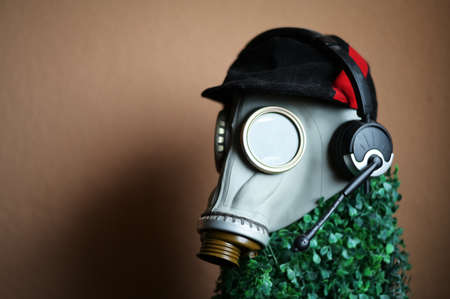 Photo of a gas mask with headphones on the head of a mannequin against the background of a wall indoors