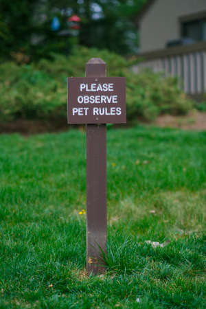 Brown plate of pet rules on grass background