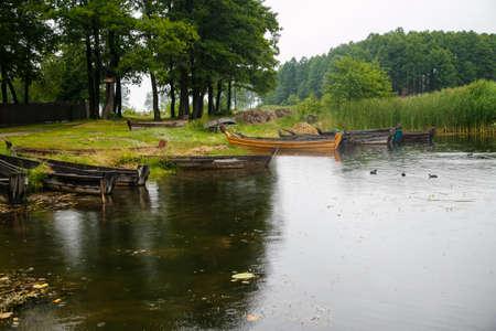 Oude houten boten aan de oever van het meer in de buurt van riet Stockfoto