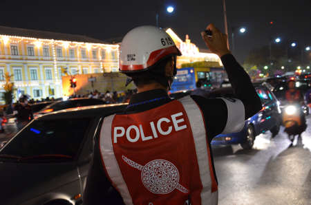 light duty: The police is working very hard through the night in crowded area of Bangkok.