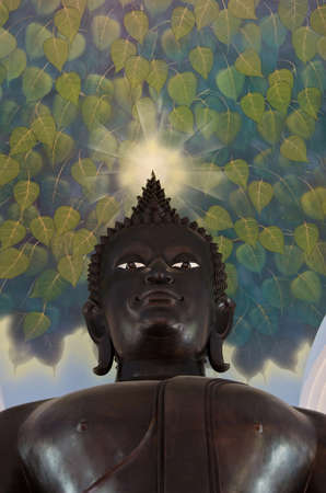 Buddha statue looking down kindly with an aura on this head shining to console all living things  photo