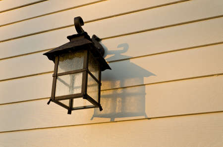 lamp shade: old-fashion lamp is hanging on the white wooden wall Stock Photo