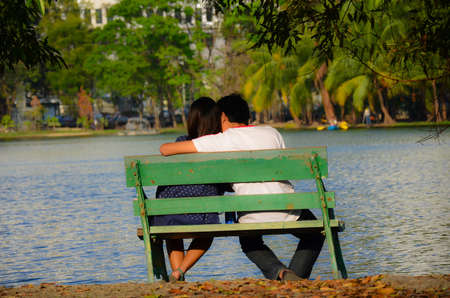 A couple is sitting near the riverside, flirting each other. photo