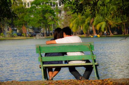 enamorados besandose: Una pareja está sentada cerca de la orilla del río, coqueteando entre sí. Foto de archivo
