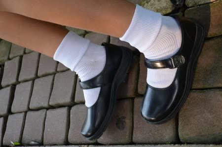 タイの女の子は学校の制服として黒革の靴を着ています。