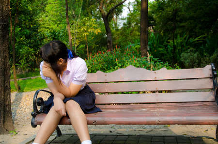 Thai student crying alone on the bench in the park.