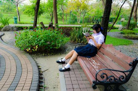 uniform skirt: Thai high-schoolgirl reading in the park. She is relaxing Stock Photo