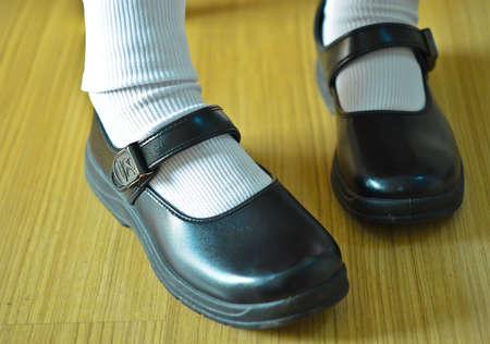 Dziewczyna tajski nosi czarne skórzane buty za mundurek szkolny.
