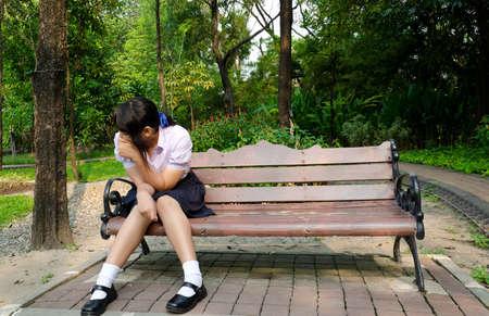 zapatos escolares: Estudiante tailand�s llorar solo en el banco en el parque Foto de archivo
