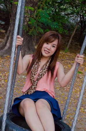 A cute Thai girl playing a swing photo
