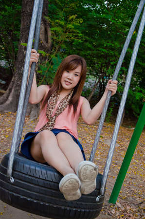 A cute Thai girl playing a swing photo