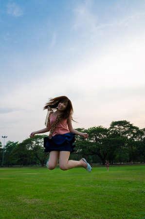 A cute Thai girl jumping with joy photo