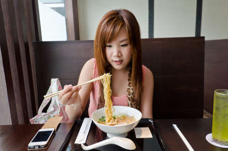 Bangkok, 2012 - A cute Thai girl is preparing to eat Japanese Ramen in the resturant call 'Chabuton'. A franchise from a famous 'Champion Ramen' in Japan. Thai office girl in urban really love it.