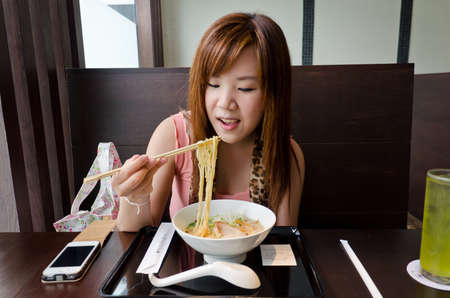 resturant: Bangkok, 2012 - A cute Thai girl is preparing to eat Japanese Ramen in the resturant call Chabuton. A franchise from a famous Champion Ramen in Japan. Thai office girl in urban really love it.