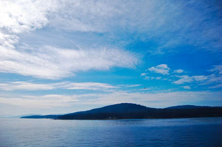 distant: Nice landscape from the sea with blue water and sky, with the highland