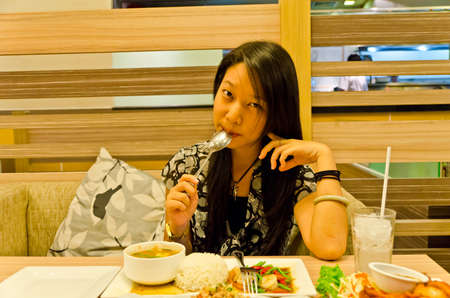 An asian (Thai) girl biting her spoon with a cute pose in front of her Thai cuisine meal Stock Photo - 13656223
