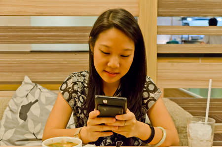 An asian (Thai) girl is playing with her mobile in the restaurant, ignoring her food Stock Photo - 13655006
