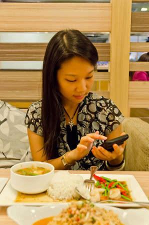 An asian (Thai) girl is playing with her mobile in the restaurant, ignoring her food photo