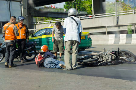 BANGKOK, THAILAND - APRIL 28: Motorcycle accidents on the street of Bangkok due to road slippery on April 28, 2012. People around that area gather to help the injury.