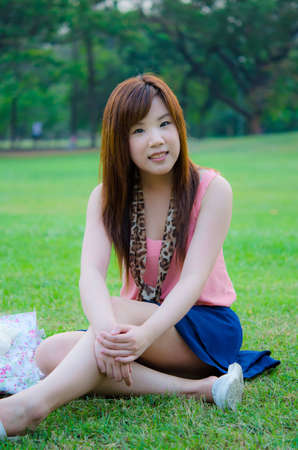 A cute Thai girl sitting sexy on the grass, relaxing in the park. Stock Photo - 13764742