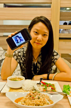 An asian (Thai) girl is showing a picture of herself in the mobile, ignoring her food photo