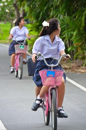 zapatos escolares: Colegiala tailandesa montando una bicicleta, en el parque. Editorial