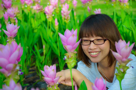 Cute Thai girl are very happy with flowers (Siam Tulip). She is laughing with joy. Stock Photo - 15739645