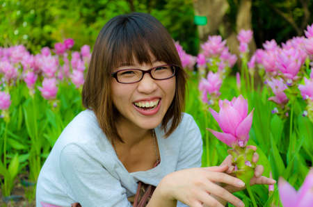 Cute Thai girl are very happy with flowers (Siam Tulip). She is laughing with joy. photo