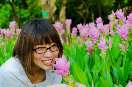 asian tulips: Cute Thai girl scent a pink Siam Tulip. She loves flowers. Stock Photo