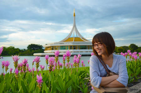 Cute Thai girl is relaxing beside the river bank, near a Siam Tulip field. Stock Photo - 15739643