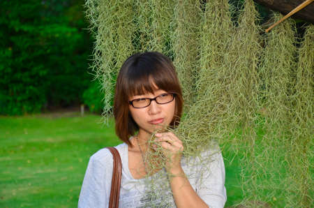 Cute Thai girl examining a Spanish Moss plant with her sense. Stock Photo - 15739649