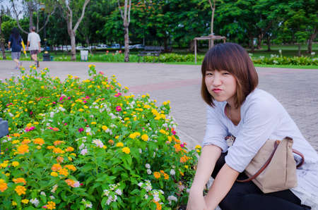 Cute Thai girl is looking at colorful  flowers. and showing cute expression. Stock Photo - 15739650
