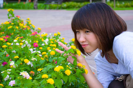 Cute Thai girl is very happy with colorful flowers. She is smelling them with joy. photo